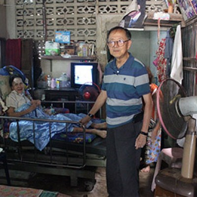 Mr. Surachai visiting with an elderly woman.